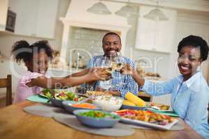 Family toasting glasses of wine and juice on dining table