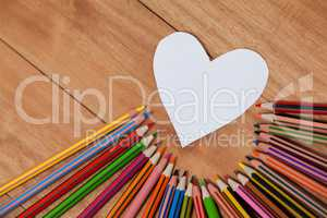 Colored pencil arranged around heart shape paper