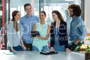 Smiling business team discussing over digital tablet in meeting