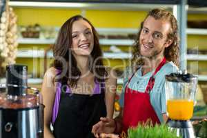 Smiling shop assistants standing together in health grocery shop