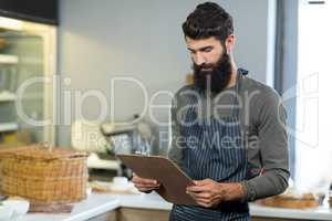 Salesman holding clipboard at counter