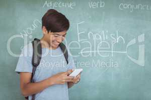Happy schoolboy with backpack using mobile phone in classroom