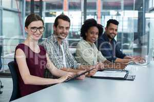 Portrait of smiling business executives sitting together in meeting
