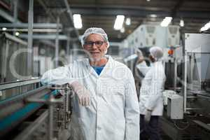 Smiling factory worker standing next to production line