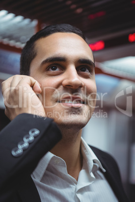 Executive talking on mobile phone in train
