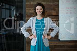 Smiling female business executive standing with hand on hip in office