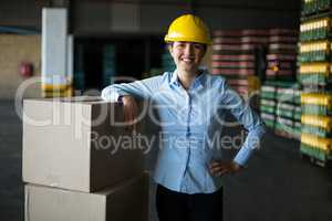 Smiling female factory worker standing with hand on hip in factory