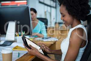 Female graphic designer smiling while using digital tablet