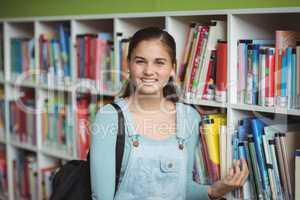 Portrait of happy schoolgirl selecting book in library