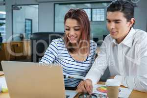 Man and woman working on laptop at desk