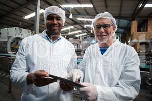 Two factory engineers with digital tablet smiling in the drinks production plant