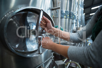 Female factory worker turning control wheel of storage tank