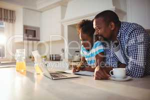 Father and daughter using laptop while having coffee