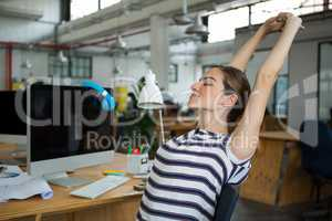 Female graphic designer sitting on chair and stretching her arms