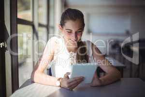 Schoolgirl using digital tablet in classroom