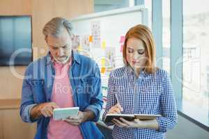 Male executive using digital tablet while female executive noting on diary