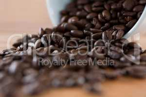Roasted coffee beans spilling out of cup