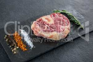 Sirloin chop, rosemary herb an spices on slate plate