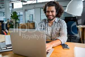 Executive using laptop in creative office