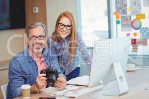 Portrait of male graphic designer holding digital camera with coworker