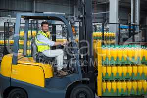 Factory worker loading packed juice bottles on forklift in factory