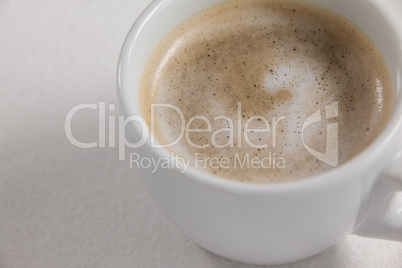 Close-up of white coffee cup with creamy froth