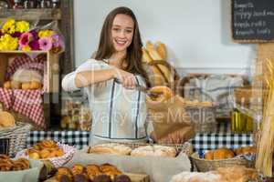 Portrait of smiling female staff putting croissant into a paper bag at counter