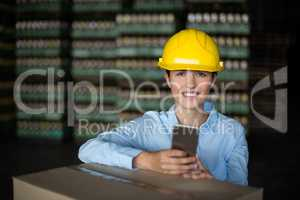Female factory worker holding mobile phone in factory