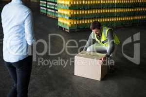 Factory worker picking up cardboard boxes in factory