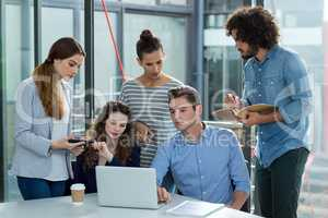 Business team discussing over laptop in meeting
