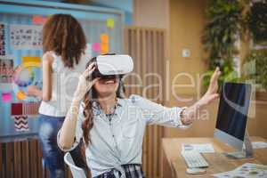 Female graphic designer using virtual reality headset with her colleague in background