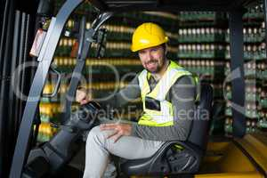 Portrait of factory workers sitting in forklift