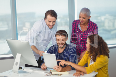 Graphic designers discussing over digital tablet