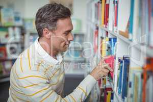 Attentive school teacher selecting book in library