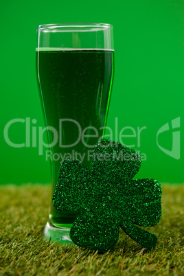 Glass of green beer and shamrock for St Patricks Day on grass