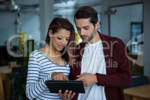 Man and woman discussing over digital tablet