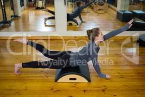 Beautiful woman exercising on arc barrel