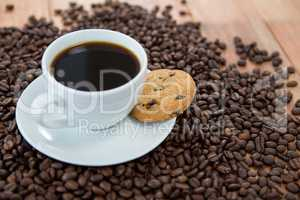 Coffee cup with cookie and coffee beans