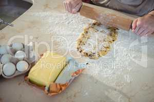 Hands sheeting the dough with rolling pin in kitchen