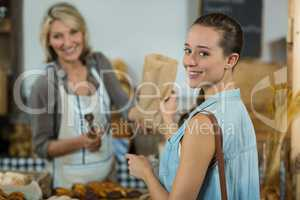 Female customer receiving a parcel from bakery staff at counter