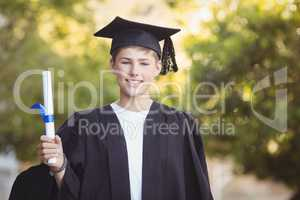 Portrait of graduate schoolboy standing with degree scroll in campus