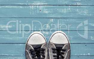 Blue men's old shabby sneakers on a blue wooden surface