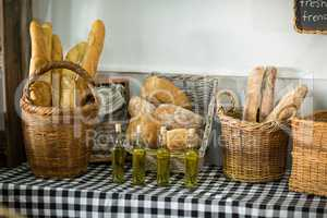 Various bread and bottle of oil on counter in bake shop