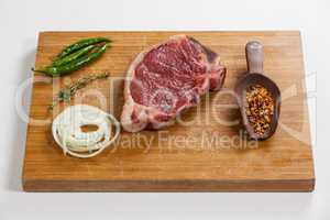 Sirloin chop and ingredients on wooden board