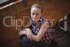 Portrait of sad schoolgirl sitting alone on staircase