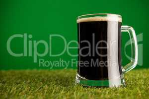Mug of green beer on grass for St Patricks Day