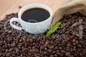 Coffee cup with coffee beans and coffee leaf
