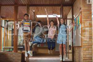 Excited classmates jumping with grade cards in corridor