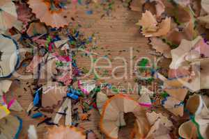 Colored pencils shavings on wooden background