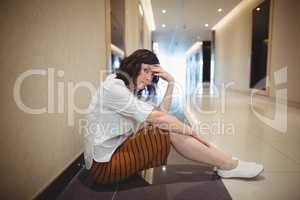 Portrait of sad female business executive sitting in corridor